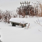 snow covered stone bench